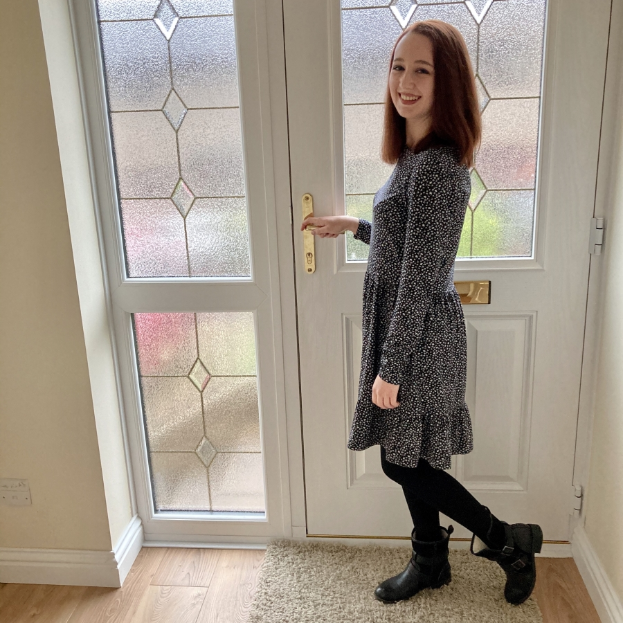 full length image of pippa indoors stood by front door, hand on the handle as of about to go out. pippa is wearing navy long sleeved dress with black heat holders tights and black boots