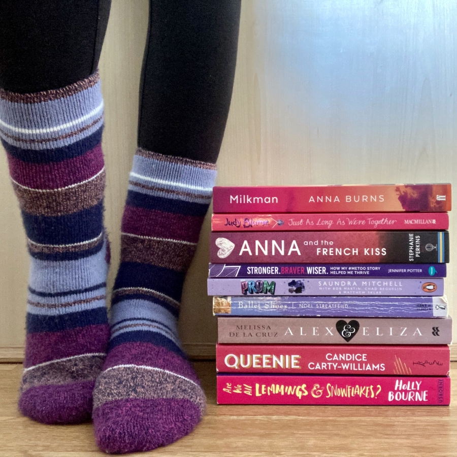 pippa's legs and feet wearing stripy purple heat holders socks, stood next to a pile of pink and purple paperback books piled up on wood floor