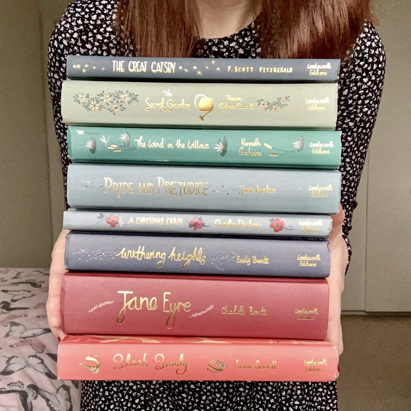 Pippa stood up holding pile of books. Pippa is wearing long-sleeved navy blue dress with tiny white spots, with brown hair down. Books are all classics from Wordsworth Collector's Editions in a rainbow spectrum of pastel colours and titles embroidered in gold. Books top to bottom are The Great Gatsby, The Secret Garden, The Wind In The Willows, Pride and prejudice, a Christmas Carol, withering heights, Jane Eyre, and black beauty.