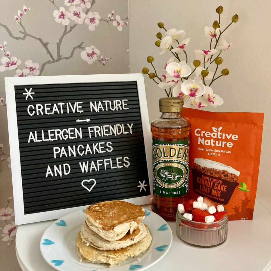 set-up of fluffy american pancakes on a plate, next to creative nature baking mix, bottle of golden syrup and a small bowl of fruit and marshmallows. letterboard in background reads 'creative nature - allergen friendly pancakes and waffles'