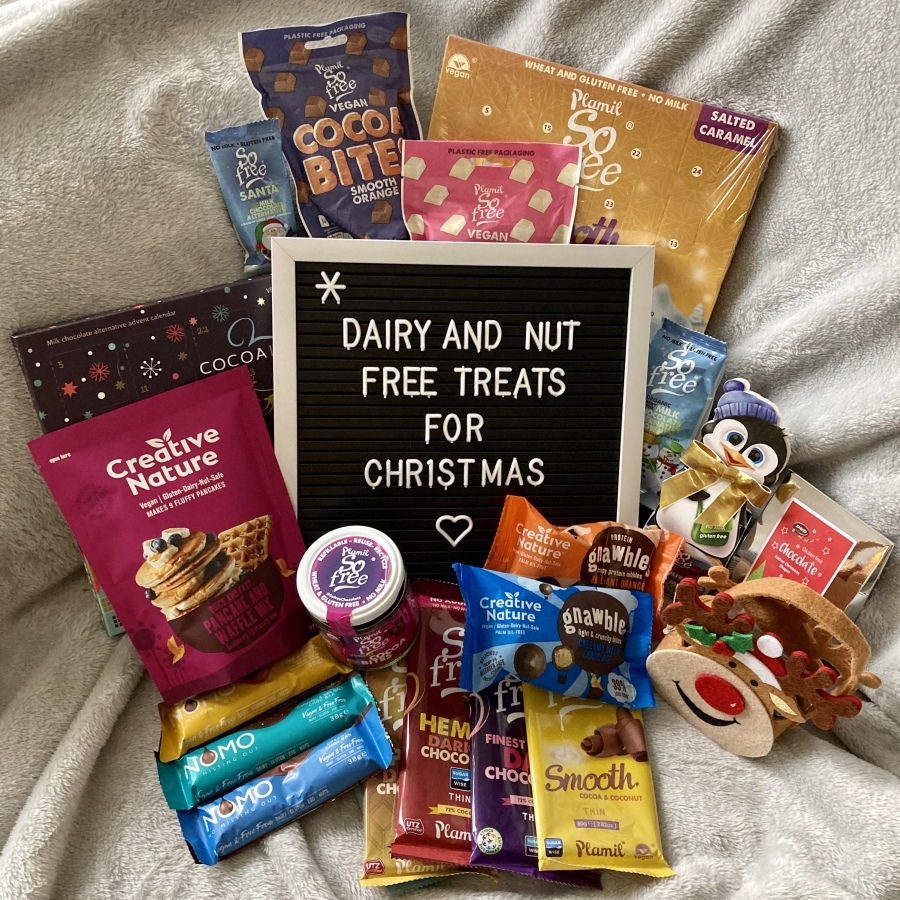 collection of free-from treats arranged on sofa, surrounding a letterboard reading 'dairy and nut free treats for christmas'