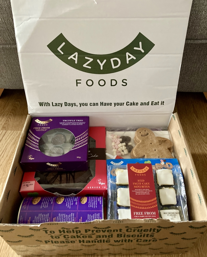 lazy days luxury christmas hamper, an open box with logo on lid, full of free-from festive treats
