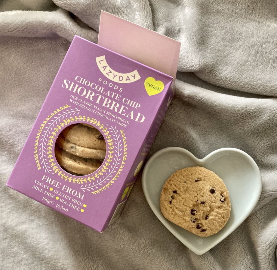 lazy days food's choc chip shortbread biscuits in small lilac box, next to a blue heart shaped plate with one shortbread biscuit on top of it