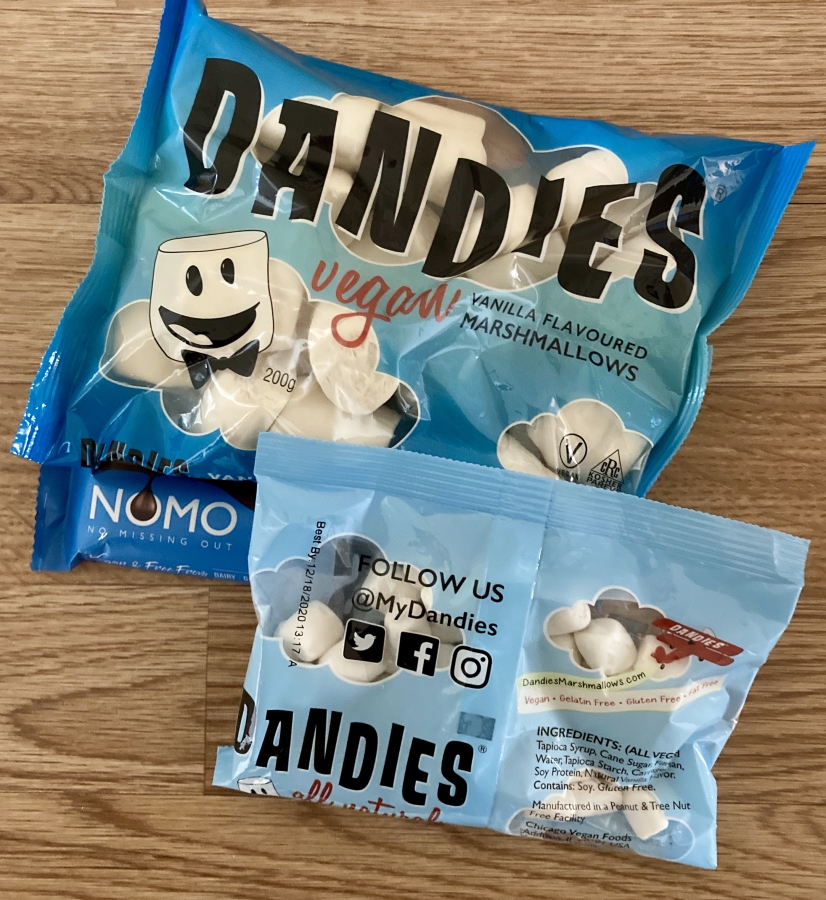 two lots of dandies marshmallows, both in blue packaging. one packet is classic vanilla in full-size, the other are mini marshmallows. blue nomo chocolate bar visible in background