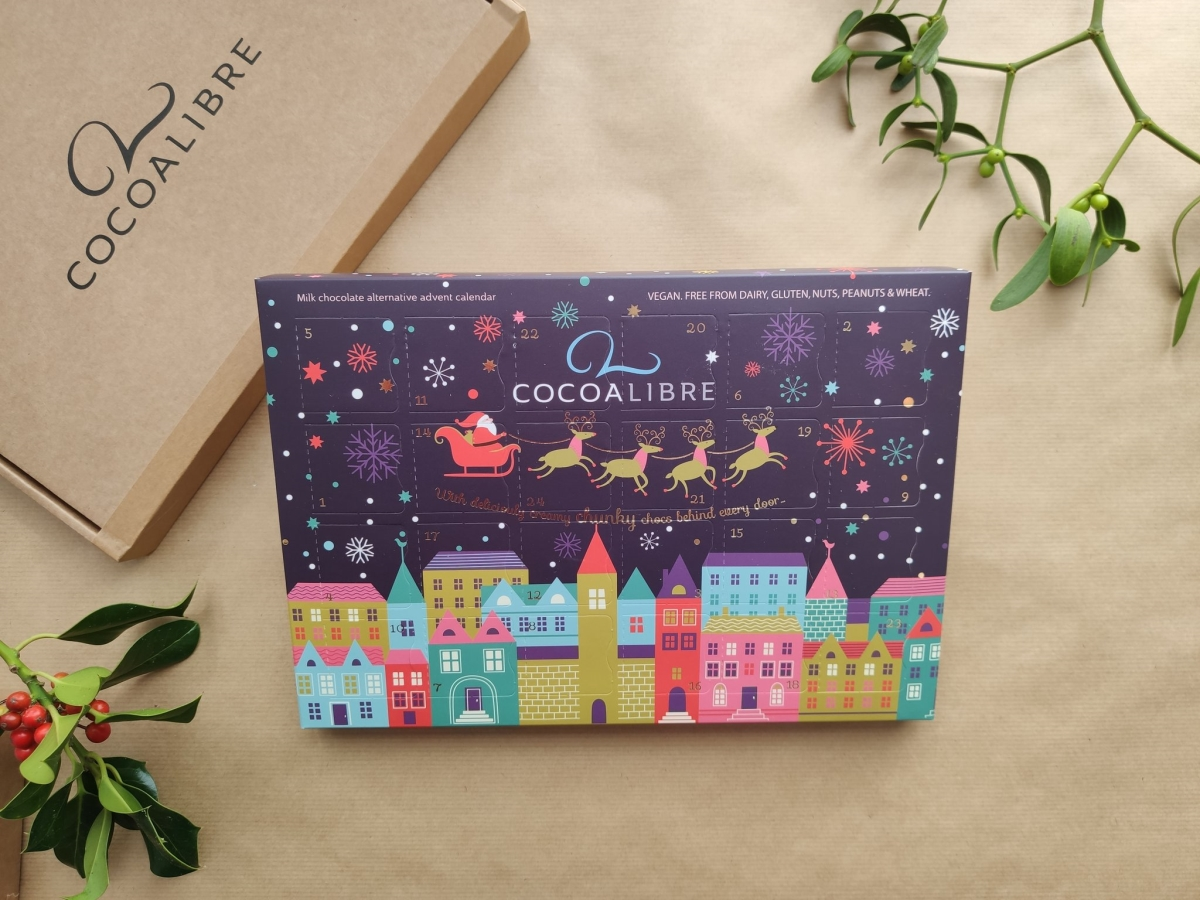 stock image of cocoa libre's advent calendar, packaged in a purple rectangular box with festive illustrations. cocoa libre branded packaging and festive leaves in background