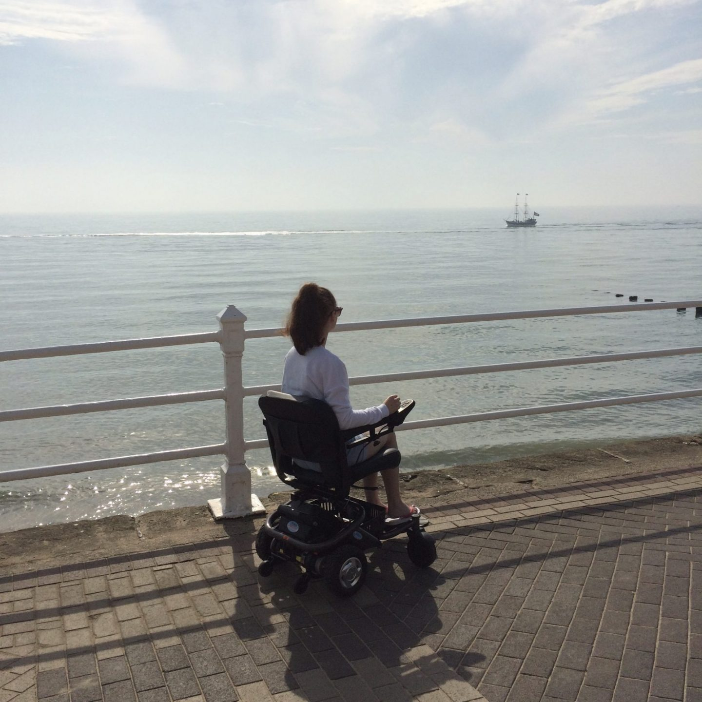 pippa using small black power-chair along the seafront, pippa turned away and looking out to sea which is visible in background