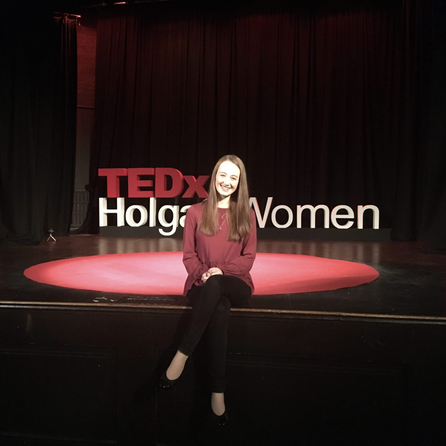 pippa sat on edge of stage at TEDx, iconic red carpet and lettering in background. Pippa is wearing a burgandy long sleeved top, black jeans and black pumps.