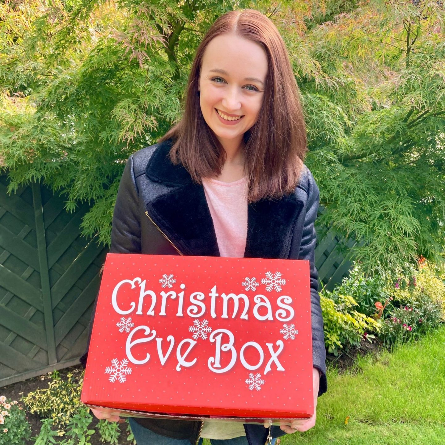 pippa stood outdoors holding up red spoonie christmas eve box and smiling