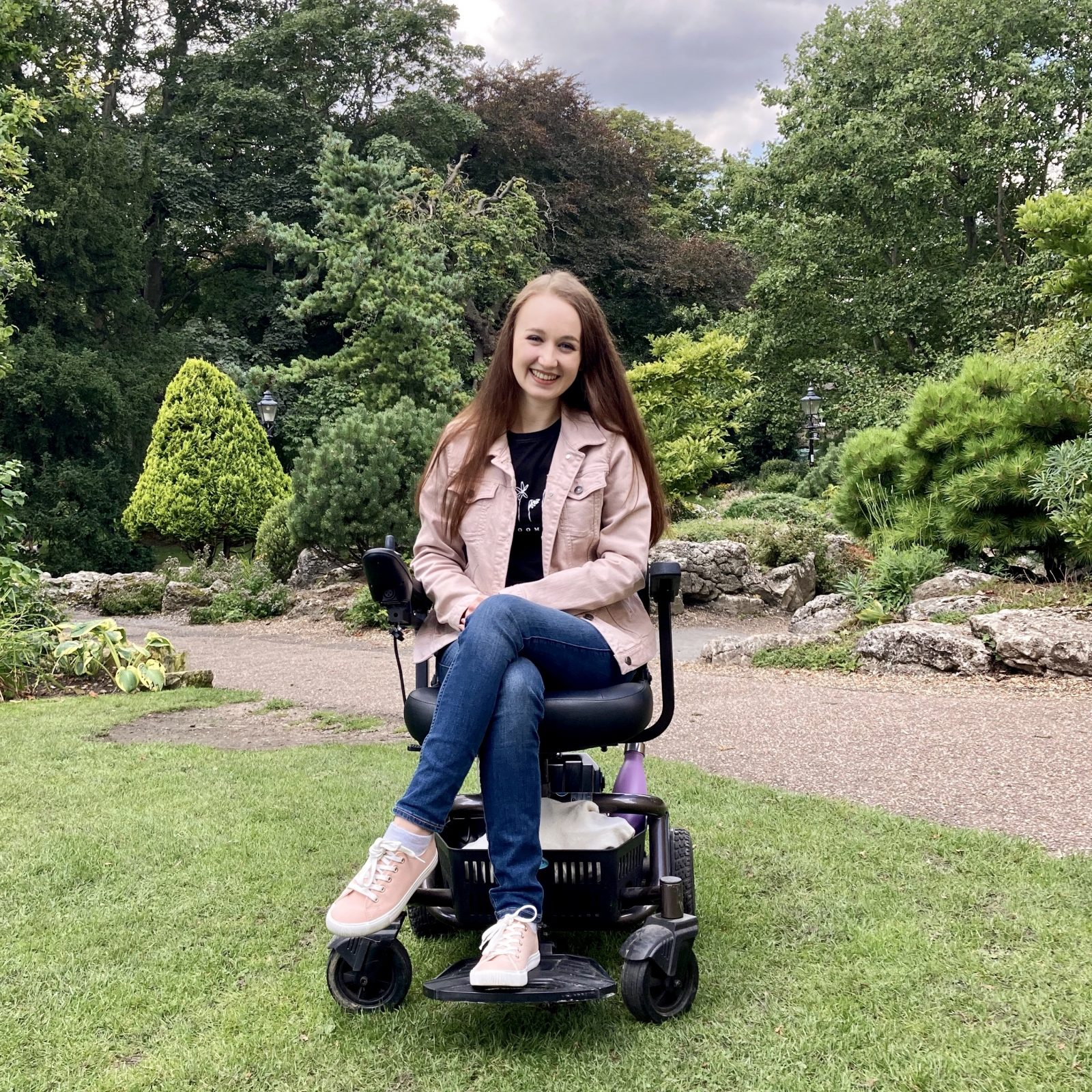 pippa outdoors in york museum gardens, surrounded by trees and grass. pippa is sat in small black electric wheelchair, smiling with hands in lap, wearing pale pink denim jacket and jeans.