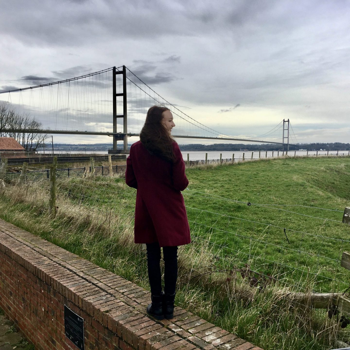 pippa stood on wall outdoors, back to camera and looking at the humber bridge in the distance. pippa is wearing a long burgandy coat with black jeans and boots