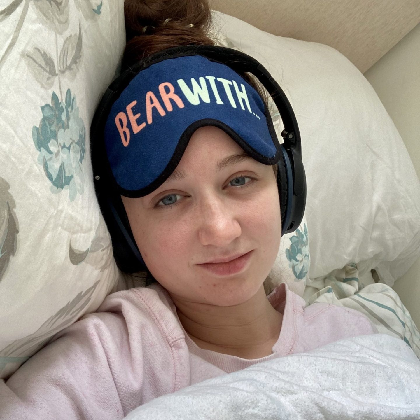 selfie of pippa in bed, no make-up and looking exhausted, wearing pink pyjamas, black noise cancelling headphones and a blue eyemask with the words 'bear with' printed on the front