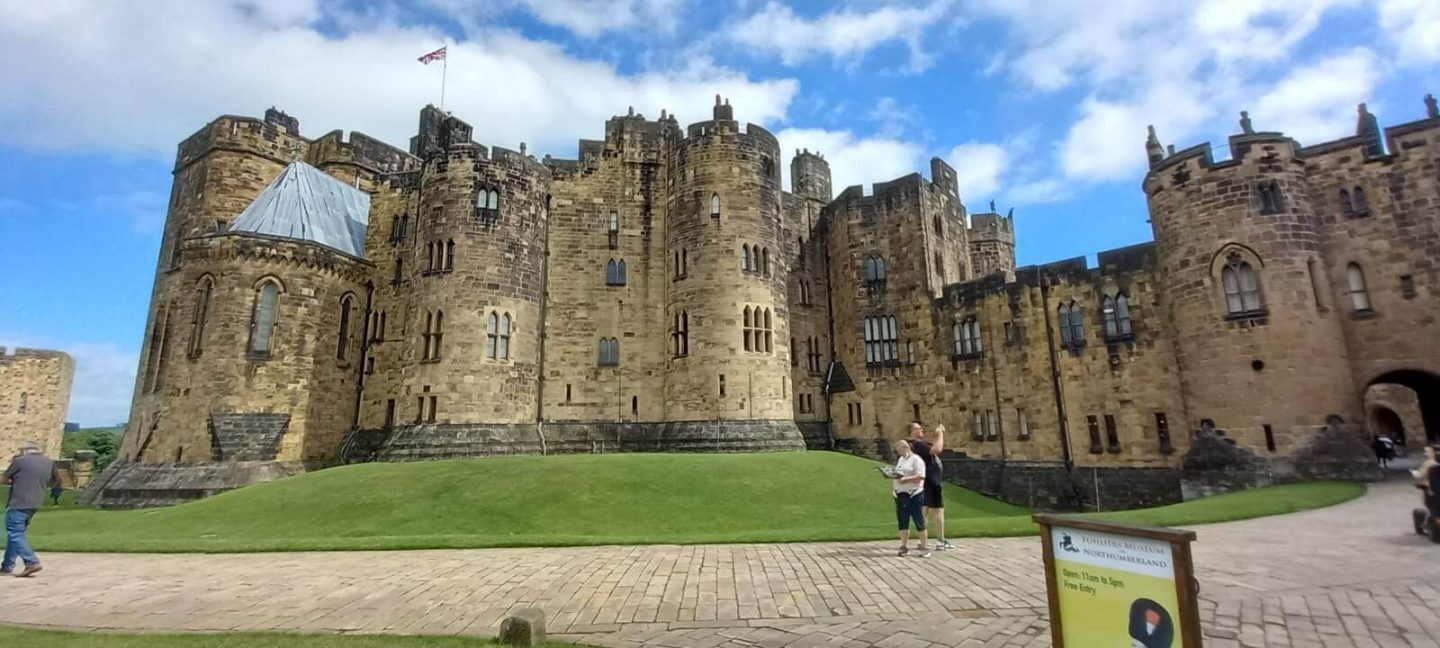 panoramic image of alnwick castle with blue skies and green grass