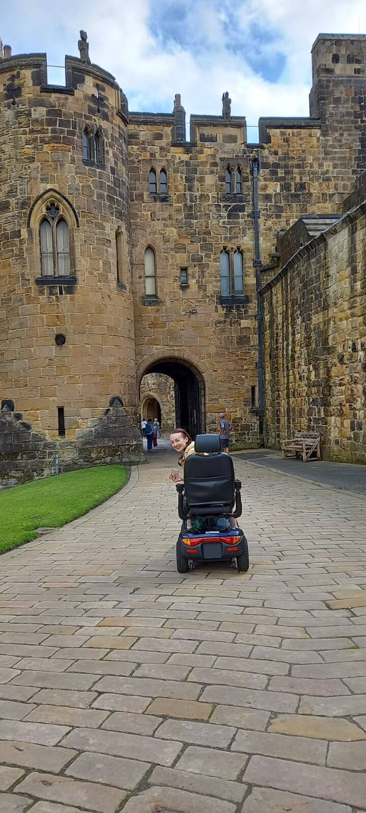 pippa driving mobility scooter along path under majestic castle walls, turning head to peek pack at camera