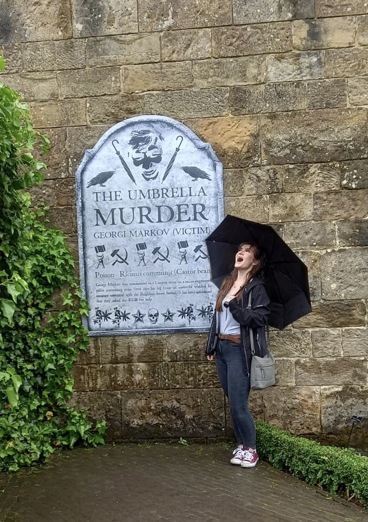 izzy stood in poision garden next to a sign about the umbrella murderer, looking on in shock while standing under her own umbrella