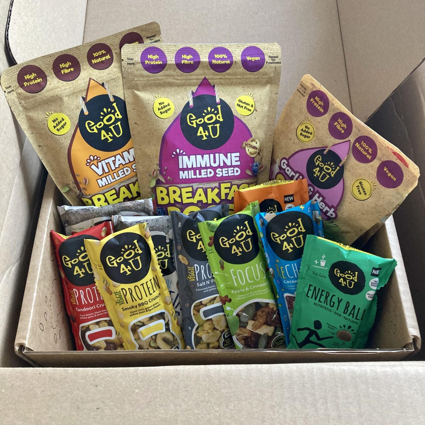 box of colourful sachets of food and snacks from good4u, including salad toppers and protein balls