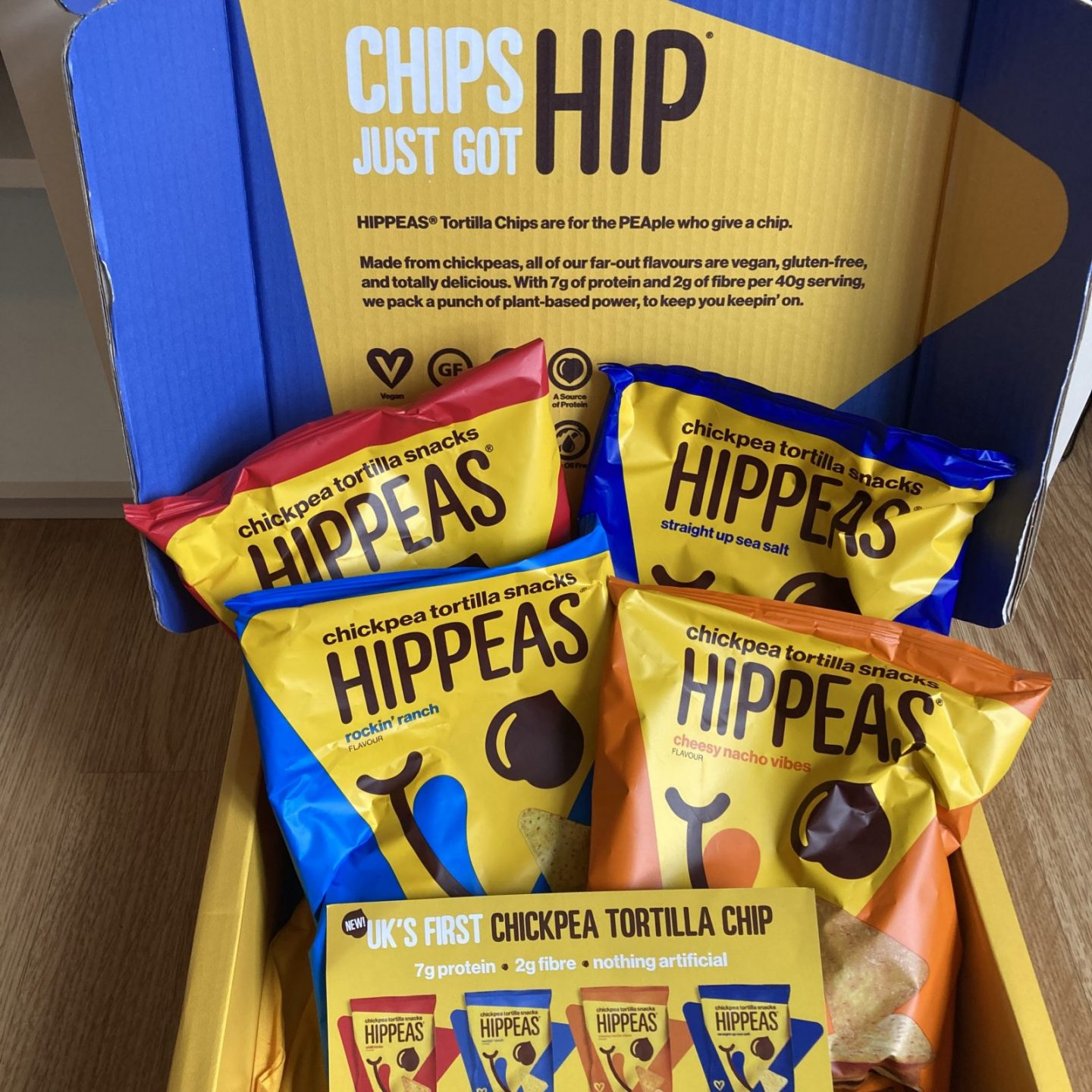 colourful box of hippeas tortilla chips in four different flavours, including yellow promotional leaflets