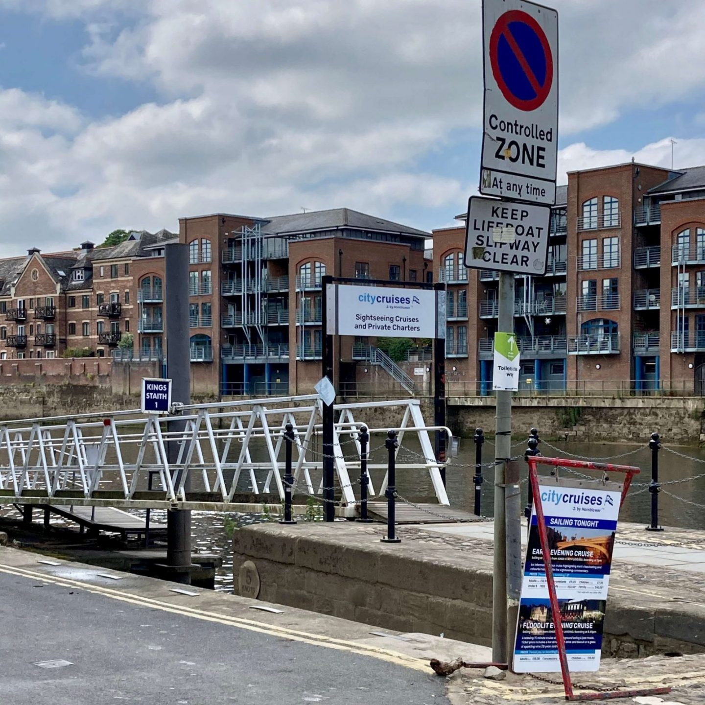 outdoor shot of king's staith landing boarding bridge, showing a long ramp from the pavement to the dock, slightly raised with white railings on both sides. city cruises banner visible in foreground