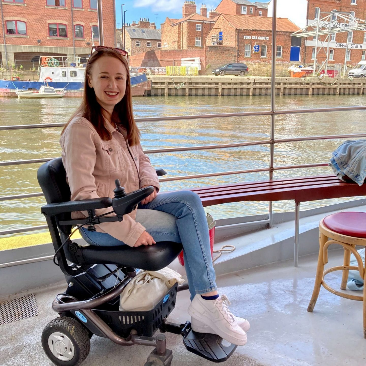pippa sat in small black powerchair on board boat, with river and dock visible in background. pippa is wearing a light pink denim jacket, blue jeans and white trainers.