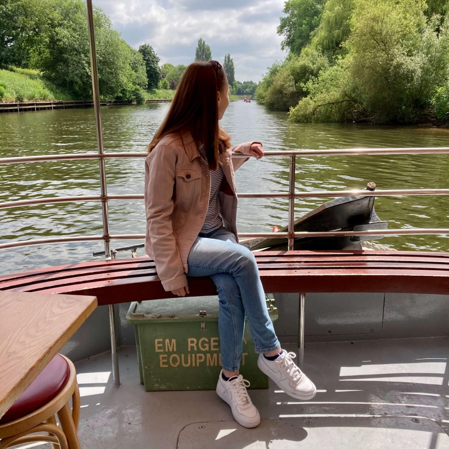 pippa sat on bench onboard boat that's out on the river, one hand on the rails and looking behind her. pippa is wearing a light pink denim jacket, blue jeans and white trainers.