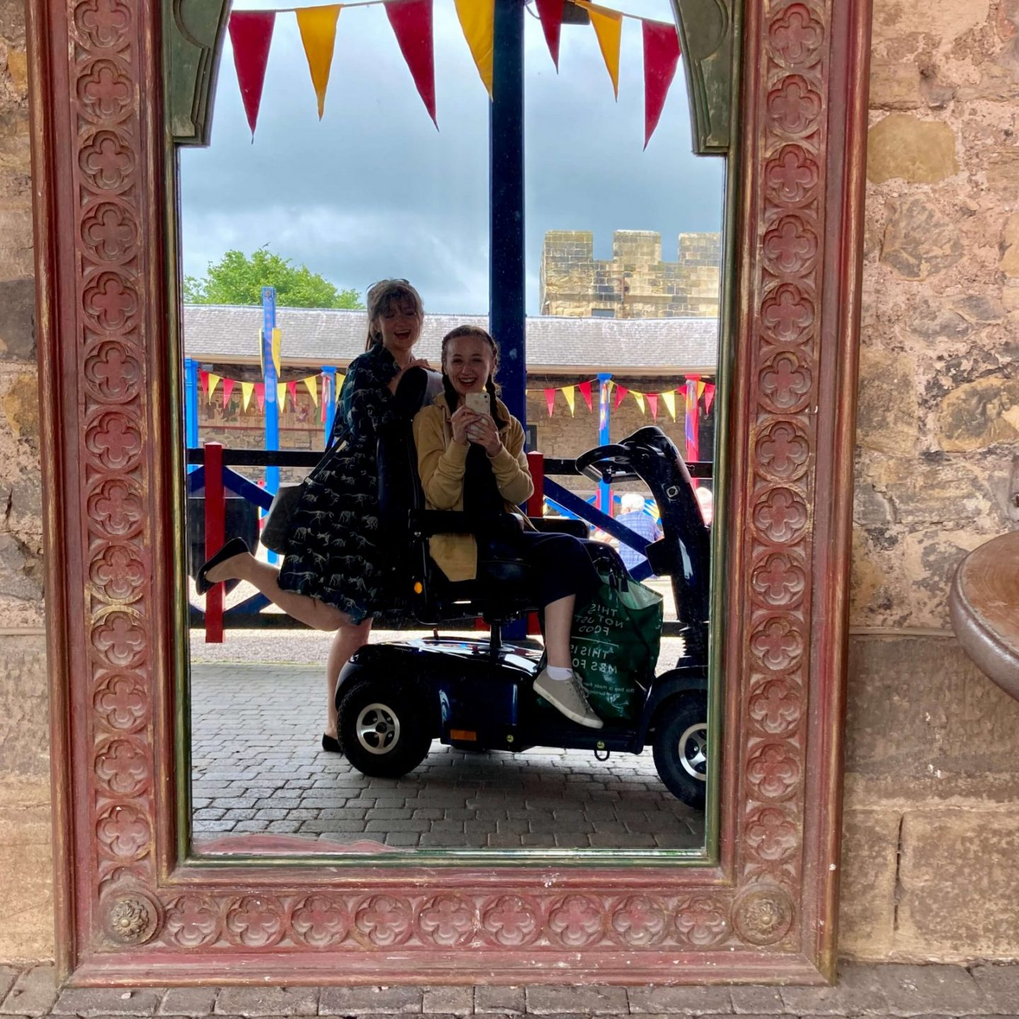 mirror selfie of pippa and izzy in medieval mirror with medieval flags and decorations visible in background. pippa is sat in mobility scooter facing the side, and izzy is posing behind her, leaning on the scooter with one leg up
