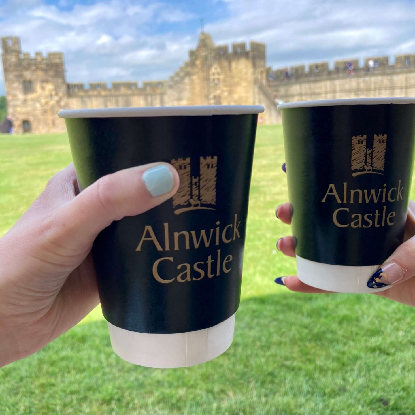 two takeaway coffee cups with alnwick castle logo, hands holding them up in front of stunning castle walls in background