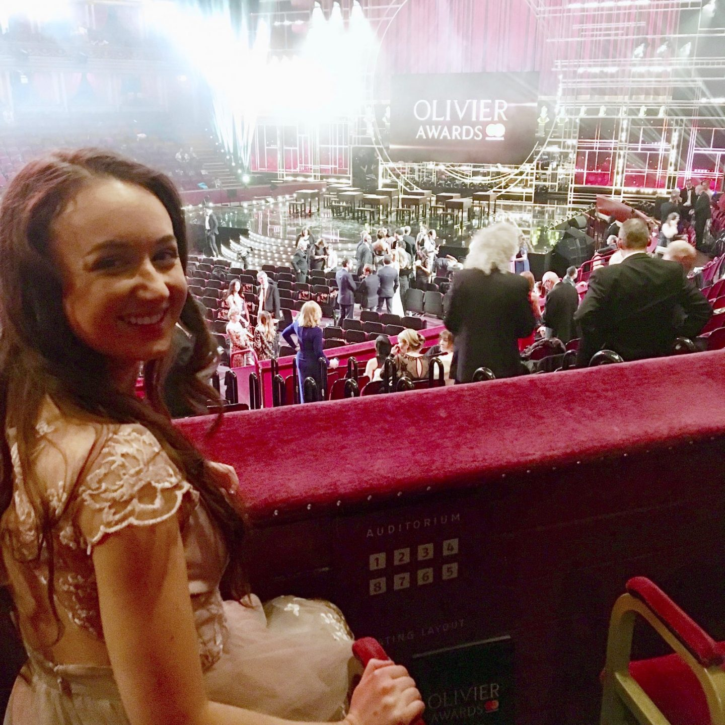 pippa sat in box at royal albert hall, looking back towards the camera. pippa is in a formal pink dress and olivier awards stage is visible in background