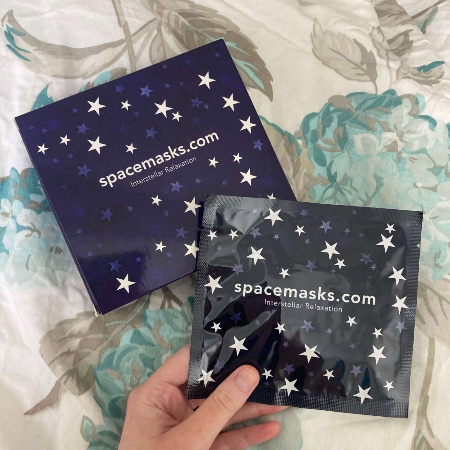 purple spacemasks packaging laid out on blue flowery bedsheets. packaging includes a square cardboard box covered with stars, and pippa's hand is holding a sachet of the same design containing one spacemask