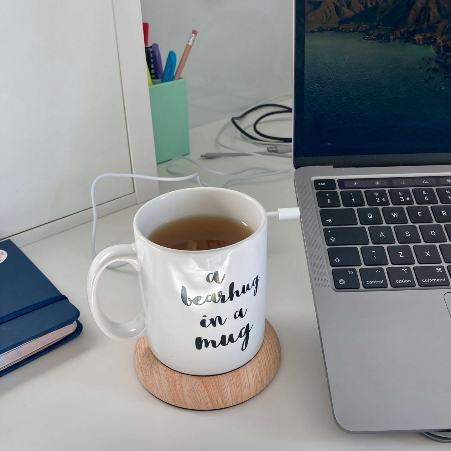 a small white mug containing green tea positioned on a USB mug warmer plugged into pippa's laptop. the mug warmer is light brown and has a pine-like texture