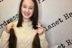 pippa with cropped hair holding locks of cut hair in hands and smiling