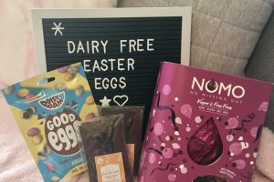 letter board reading 'dairy free easter eggs', laid on grey and pink cushions and surrounded by easter chocolate and confectionary