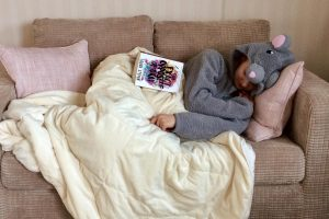 pippa laid on sofa in mouse onesie, under duvet with open book resting on top
