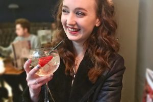 pippa sat in bar, holding up gin glass adorned with strawberries and looking off to the side