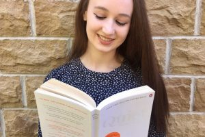 headshot of pippa outdoors in front of brick wall, hair down and wearing dark blue spotted dress, looking down at open book and smiling. book is 'quiet' by susan cain, plain white cover
