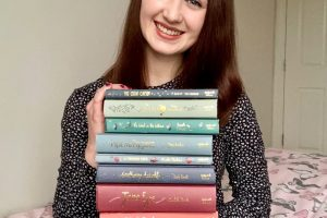Pippa sat on edge of bed, holding up a huge pile of books and smiling. Pippa is wearing long-sleeved navy blue dress with tiny white spots, with brown hair down. Books are all classics from Wordsworth Collector's Editions in a rainbow spectrum of pastel colours and titles embroidered in gold. Books top to bottom are The Great Gatsby, The Secret Garden, The Wind In The Willows, Pride and prejudice, a Christmas Carol, withering heights, Jane Eyre, and black beauty.