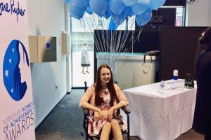 pippa in wheelchair wearing formal flowery dress and pink heels, in front of a yorkshire women of achievement photo board with pale blue balloons in background