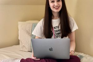 pippa sat on bed, legs crossed with laptop open and resting on knees. Pippa is wearing comfy clothes and has long brown hair down, smiling at camera