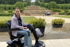 pippa sat in small black mobility scooter facing the side, at the alnwick garden with the grand cadcade waterfall feature in the background. pippa is wearing a lilac rain coat, jeans, and grey trainers, hair in two french plaits and smiling