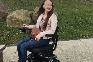 pippa in powerchair looking to right and laughing